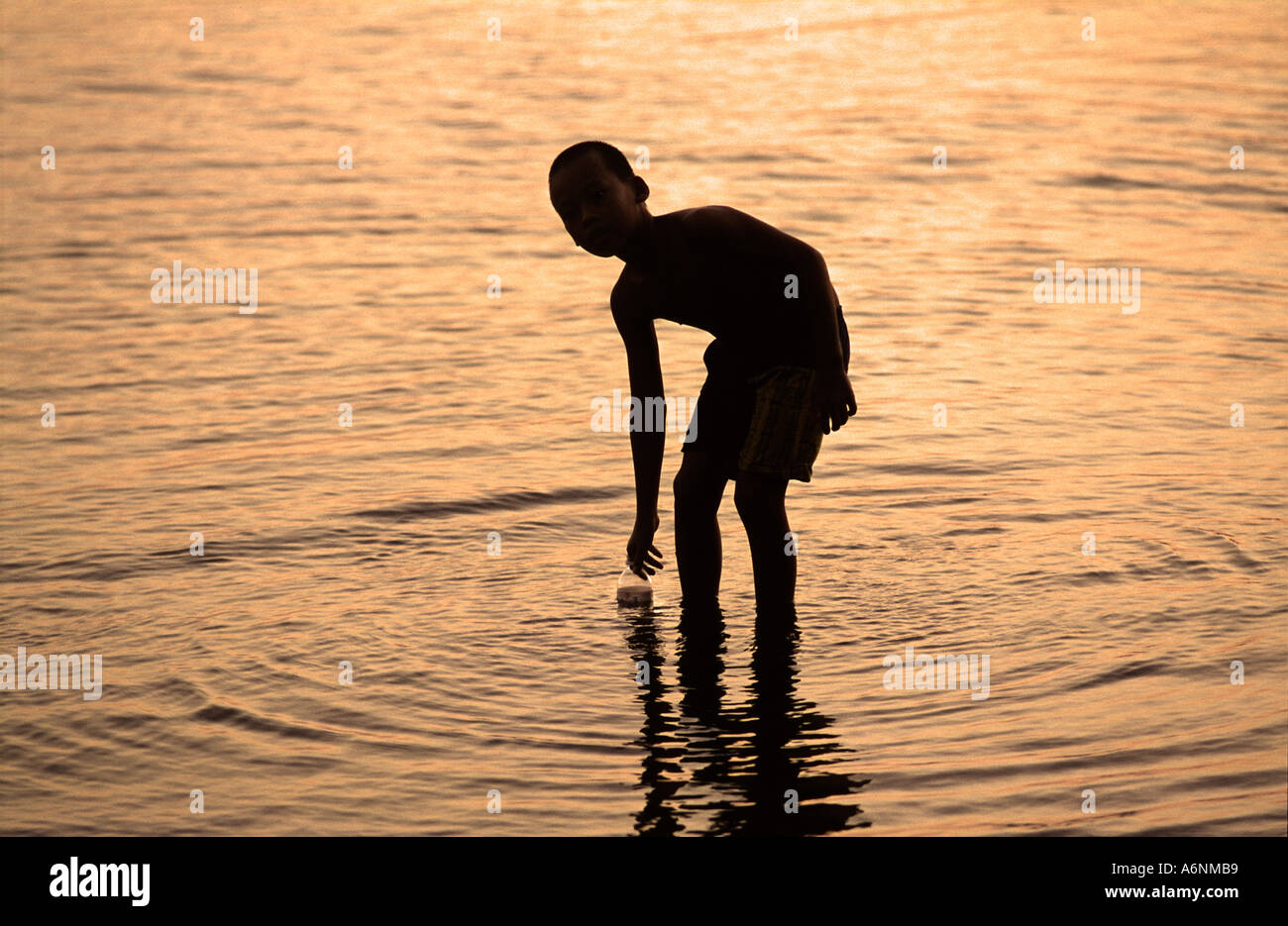 Balinese boy from the fishing port of Labuan Lalang collecting water in a bottle silhouetted Bali Indonesia - Stock Image