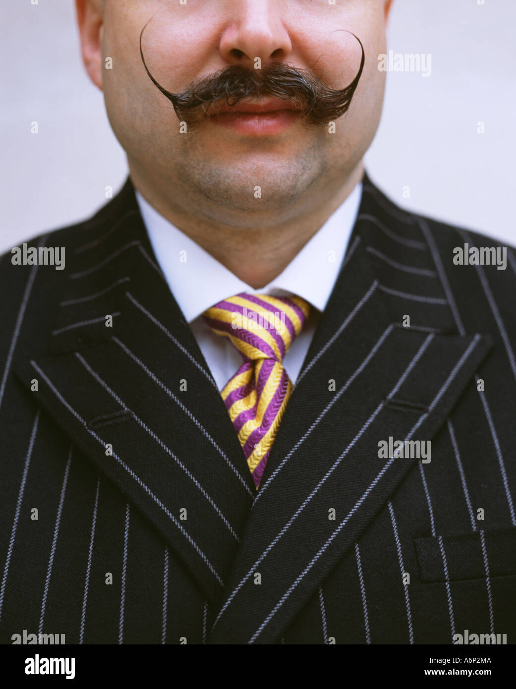 Close up of a man wearing a suit with a Salvador Dali moustache - Stock Image