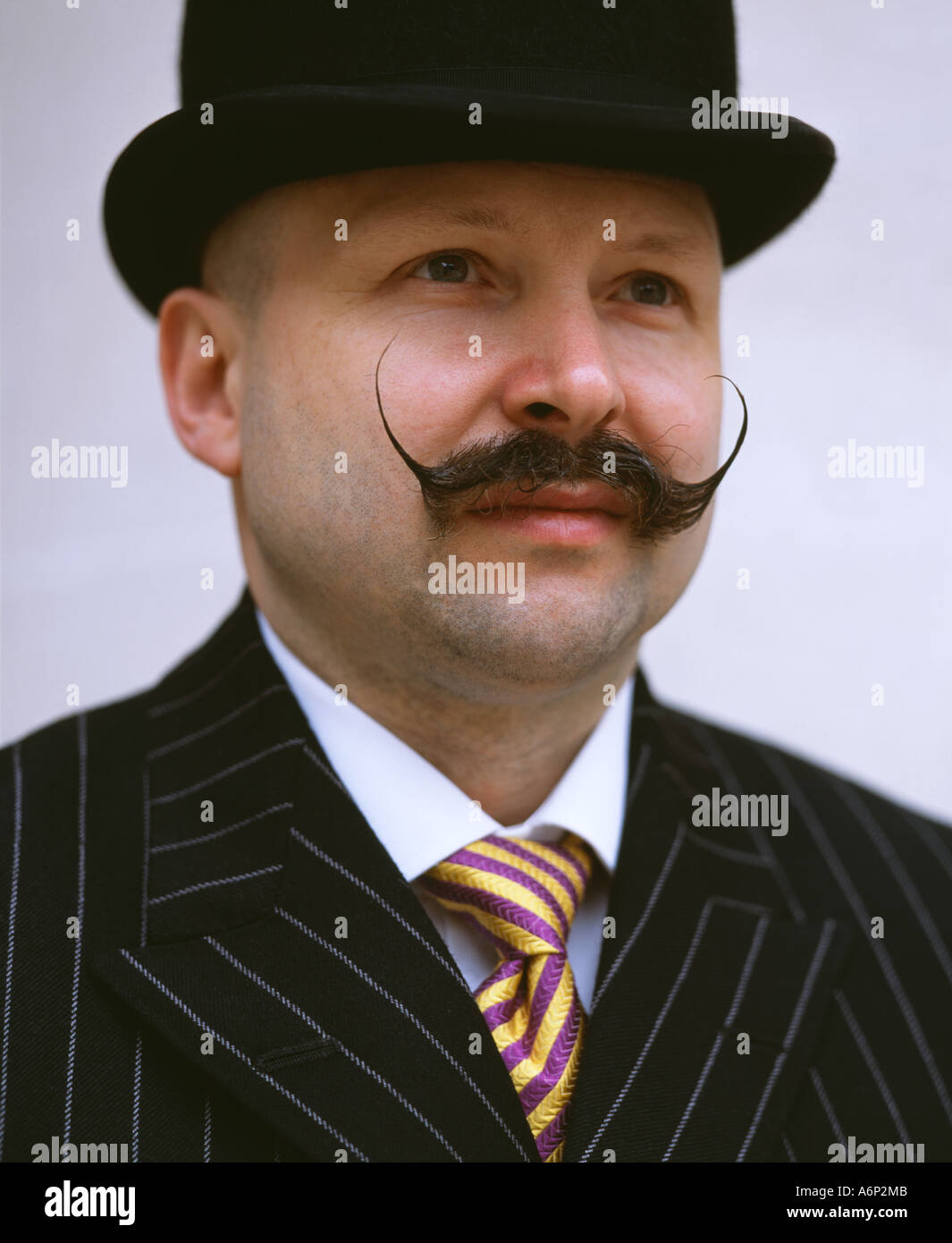 Man wearing a suit with a Salvador Dali moustache - Stock Image