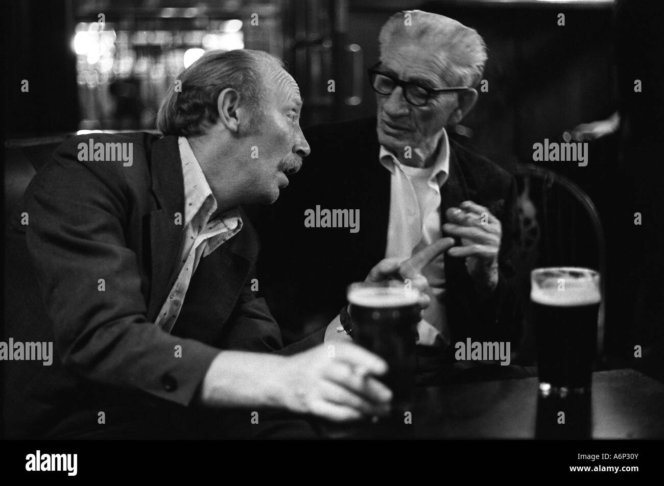 Men drinking beer chatting talking over a pint of beer in a pub 1970s Britain UK 70s HOMER SYKES - Stock Image