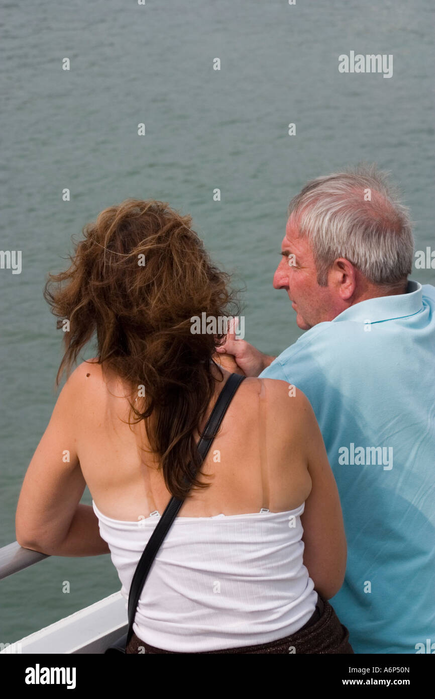 Couple male and female chatting whilst leaning on rails of ferry returning to England Boulogne sur Mer Pas de Calais Stock Photo