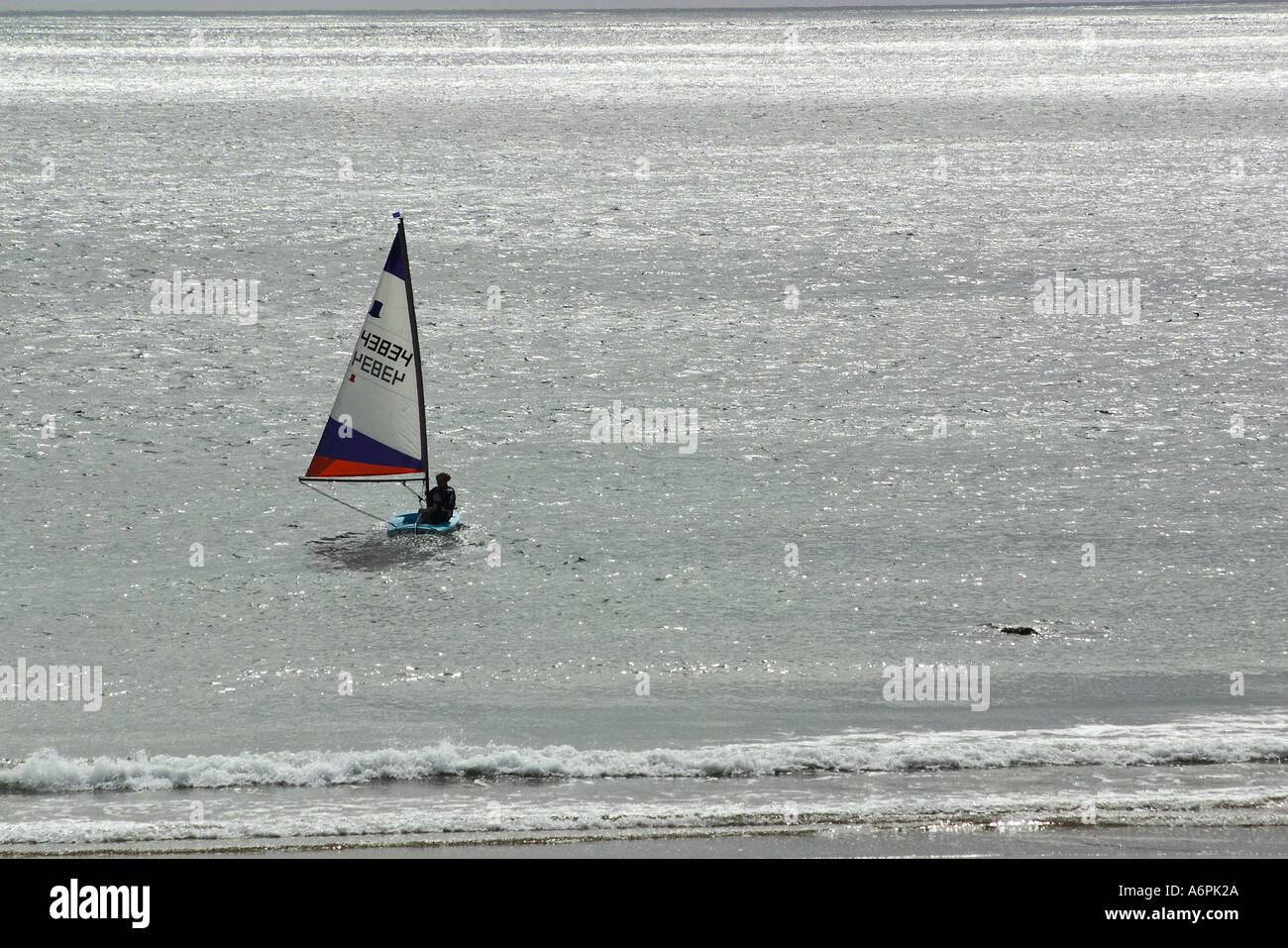 Small sail boat heading out to sea - Stock Image