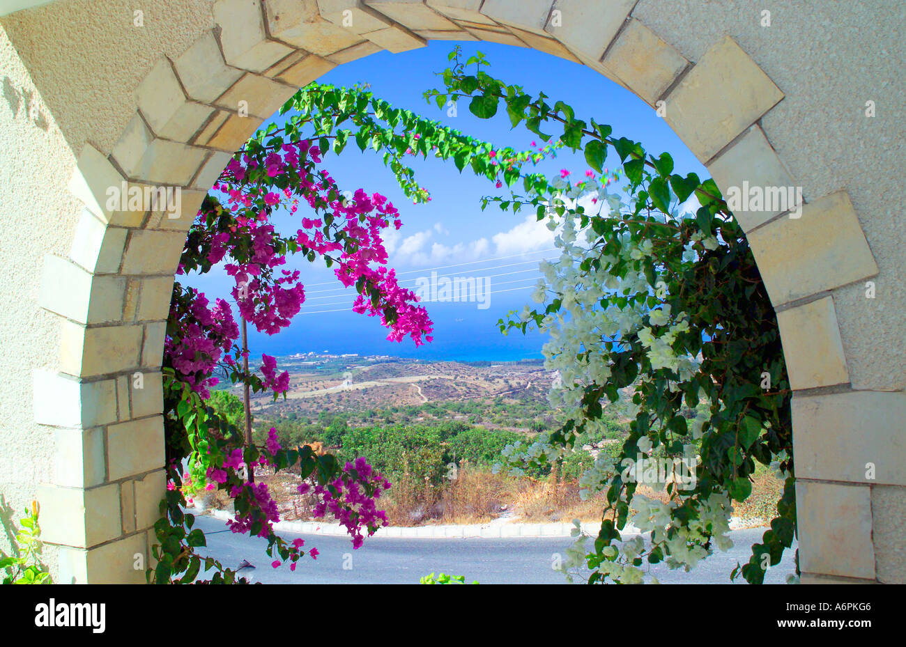 SUNNY VIEW OF THE SEA THROUGH A STONE ARCHWAY WITH FLOWERS AND HILLS AND BLUE SKY IN BACKGROUND - Stock Image