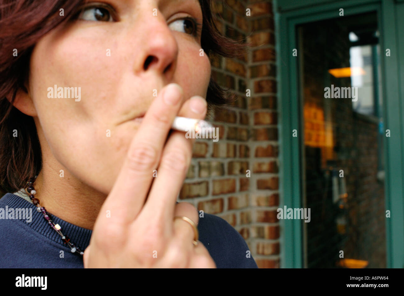 Young woman 30 with dark hair smoking on a cigarette - Stock Image