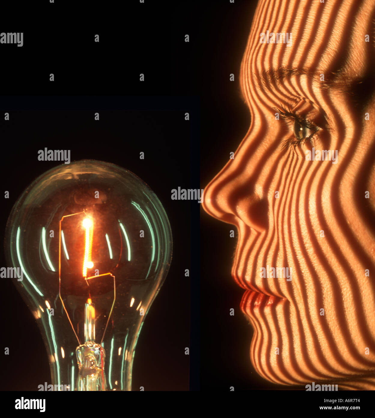 stripes projected on  face of a woman looking at light bulb abstract - Stock Image