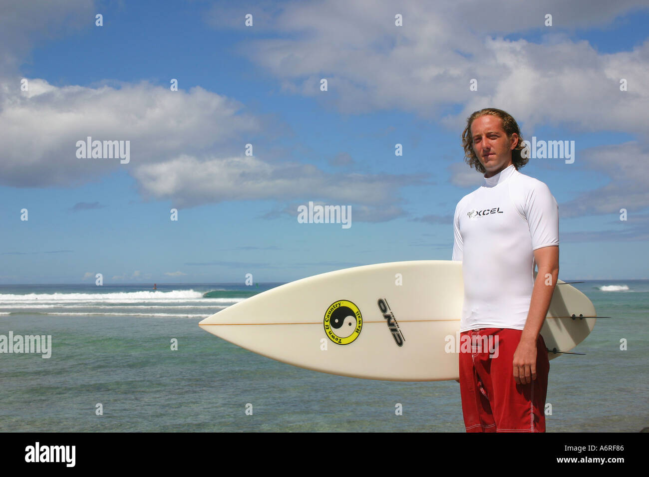 Man in white rash guard holding surfboard against partly cloudy sky and ocean waves in background Honolulu Oahu - Stock Image