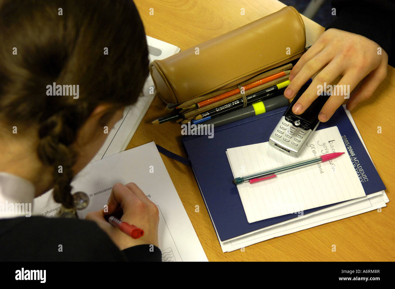 desk work study kid theft child school student youth young youngster technology mobile phones cameraphones video Stock Photo