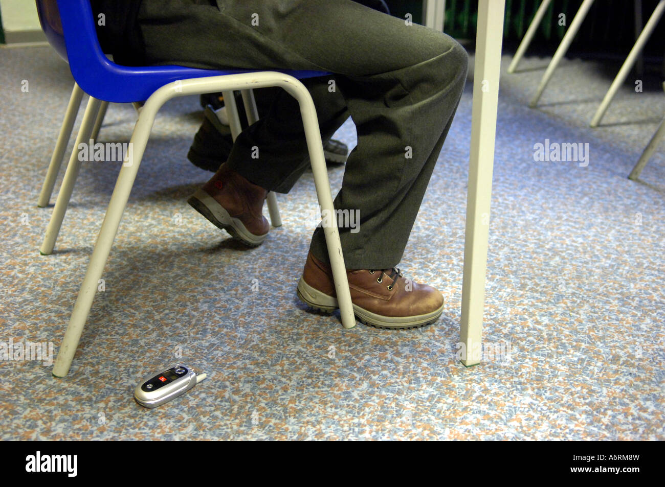floor feet legs boy male classroom lost dropped misplaced  work study kid abandoned child school student youth young - Stock Image