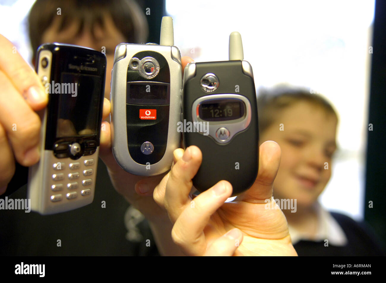 kids hold holding children school students youth young youngsters technology mobile phones cameraphones video record - Stock Image