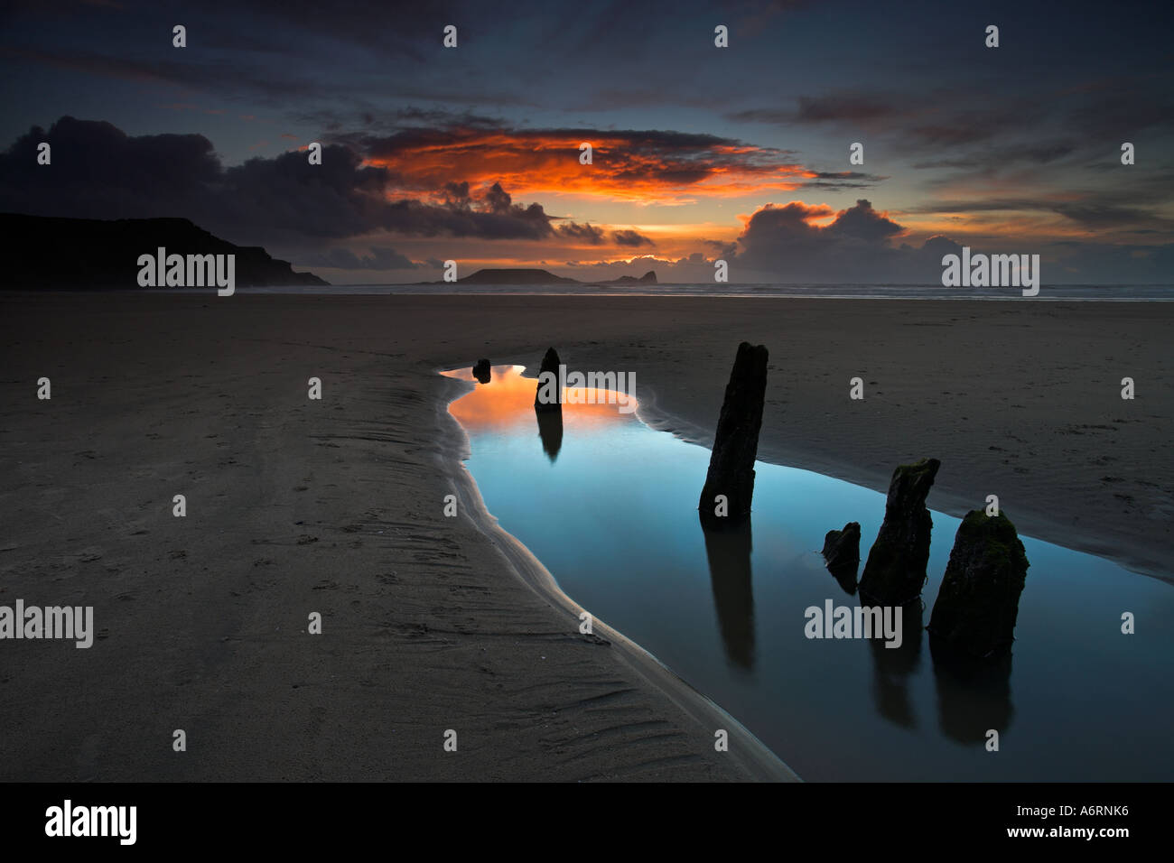 The remains of the wreck of the ship Helvatia lay on Rhossili Bay in the Gower, with the Worms Head in the background, Wales - Stock Image