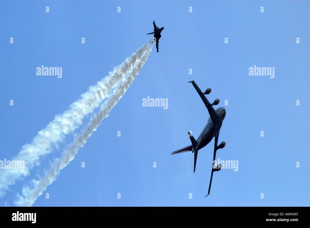 ASB77303 Commercial airliner fly past with fighter aircraft during air show - Stock Image