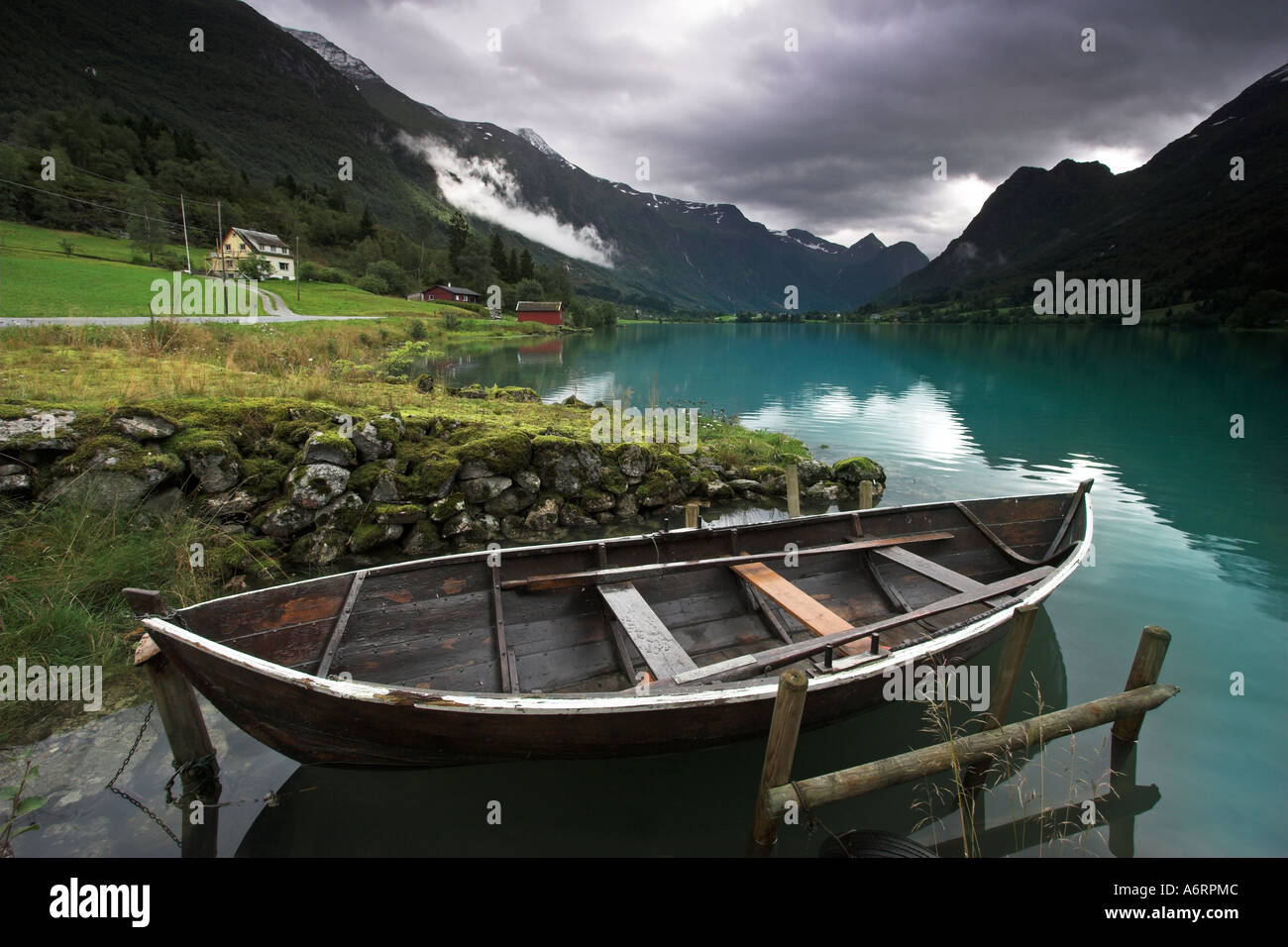 A Norwegian rowing boat lies tethered in the mirror like turquoise water of Lake Olden, Norway - Stock Image