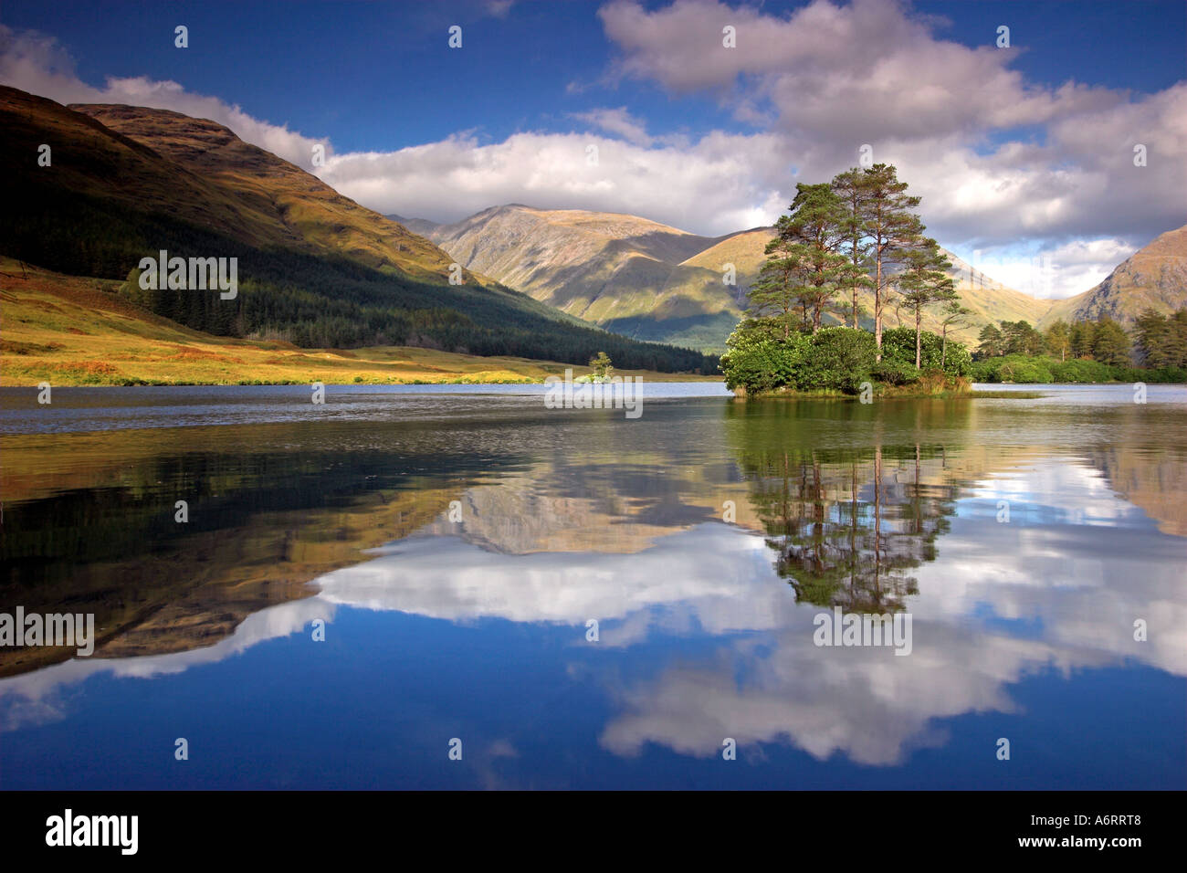 A perfect reflection at Glen Etive in the Scottish Highlands.  The single island, bathed in sunshine sits proudly on the Loch. - Stock Image