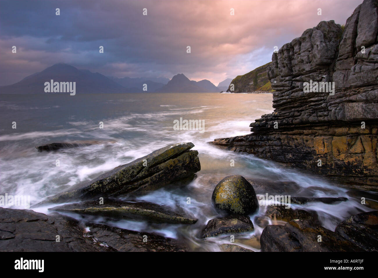 The rock strewn coast of Elgol, Isle of Skye on a dramatic morning.  High tide surges around the boulders. - Stock Image