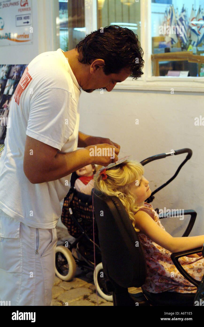 Man plaits small girls hair Skiathos town Greece - Stock Image
