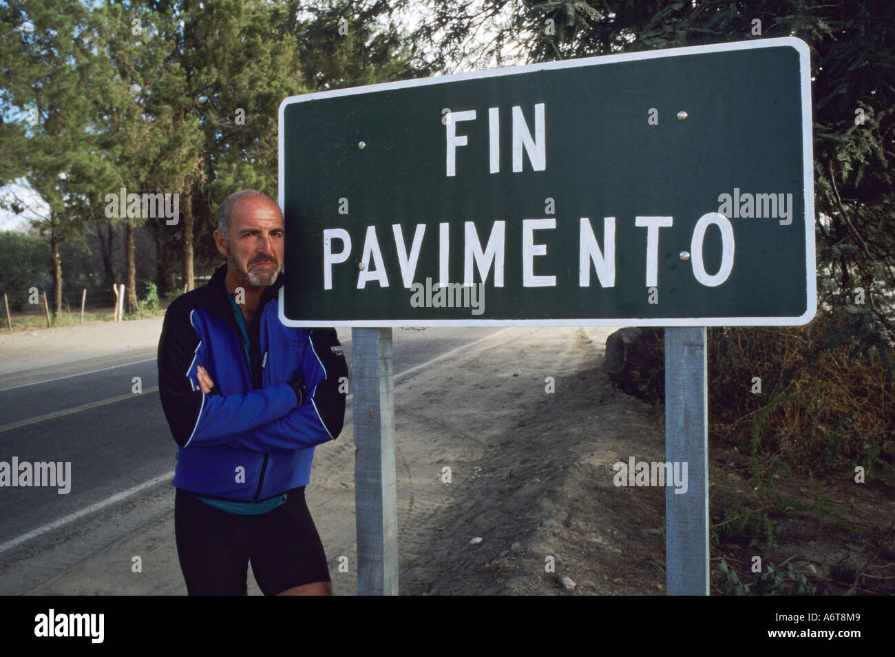 Unhappy male cyclist next to Fin Pavimento end of Tarmac sign in Argentina Stock Photo