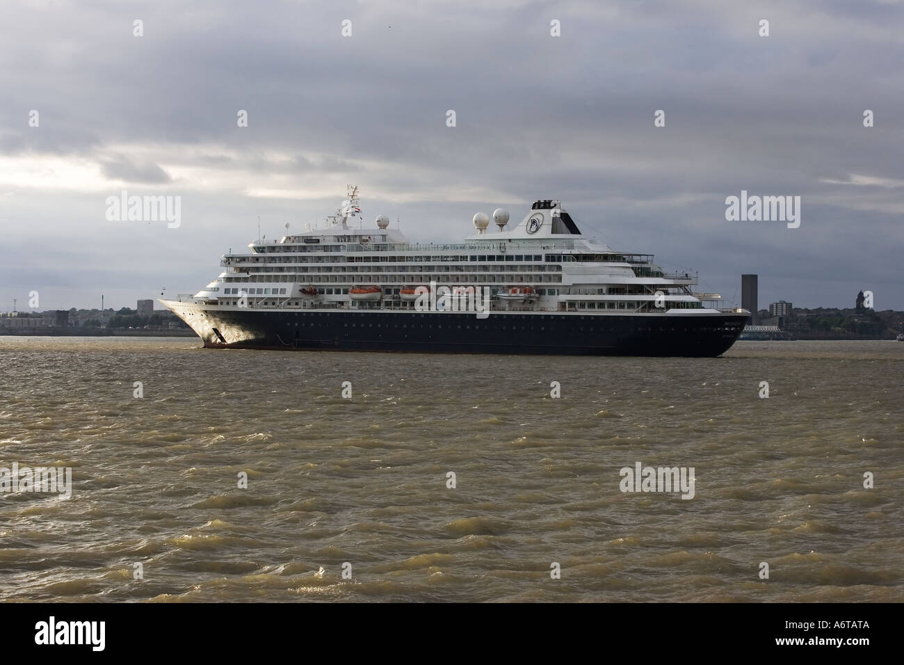 Holland America Line Prinsendam Rotterdam on her way out to sea sails up the Mersey with the Wirral in the background - Stock Image