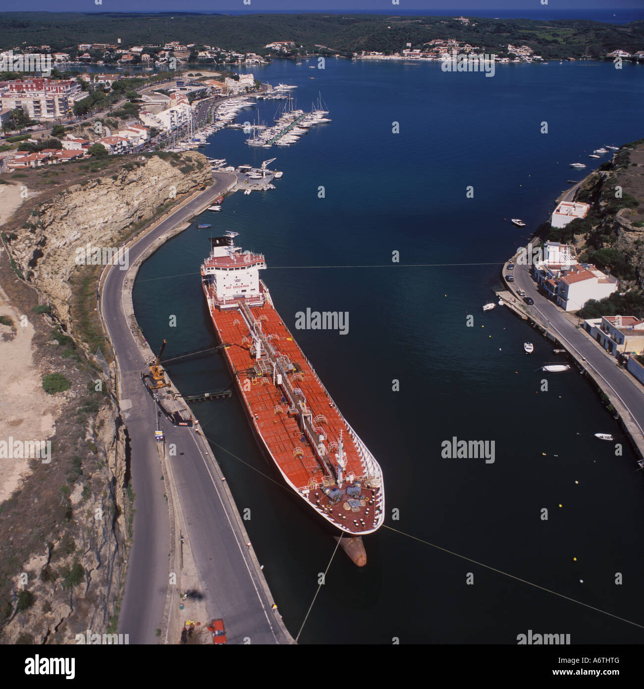 Aerial image looking North over the oil terminal ( with petroleum product carrier discharging ) and Mahon Yacht Stock Photo