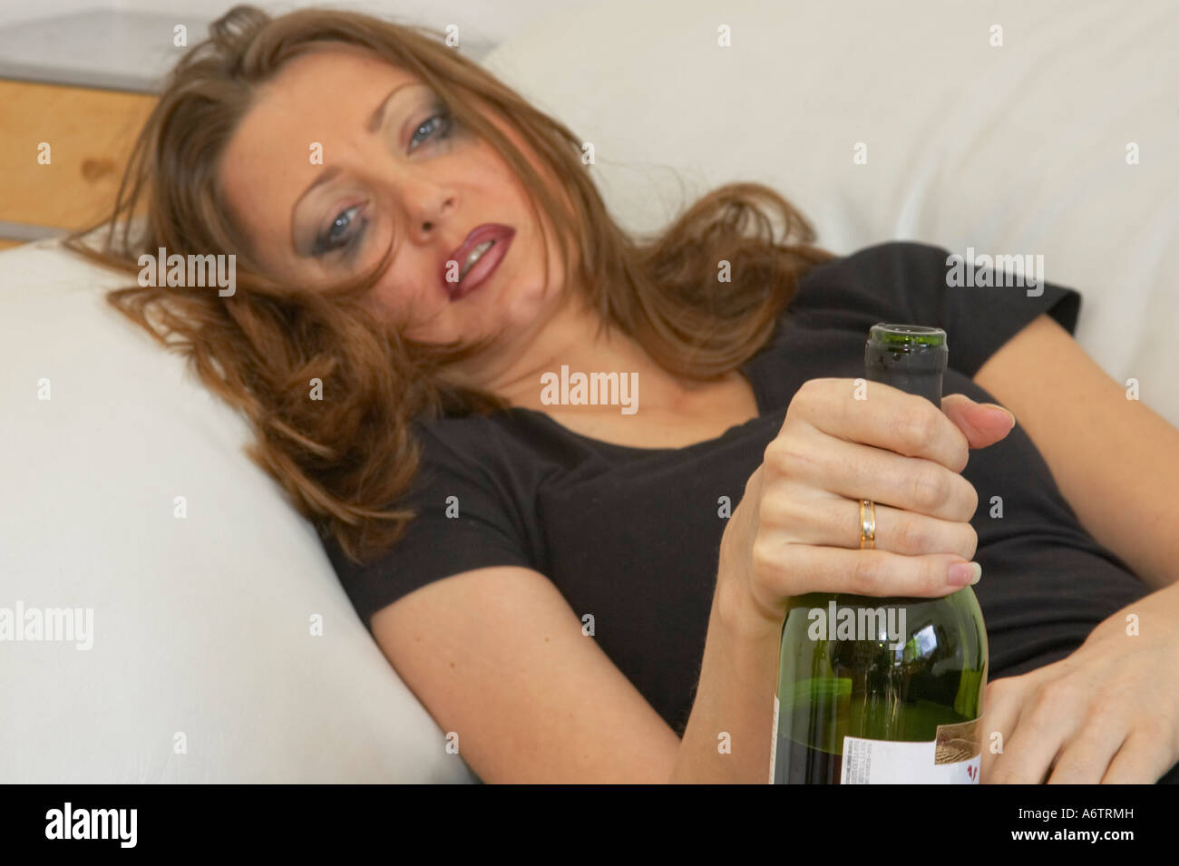 Young Woman Lying On Couch After Drinking Too Much Holding Wine