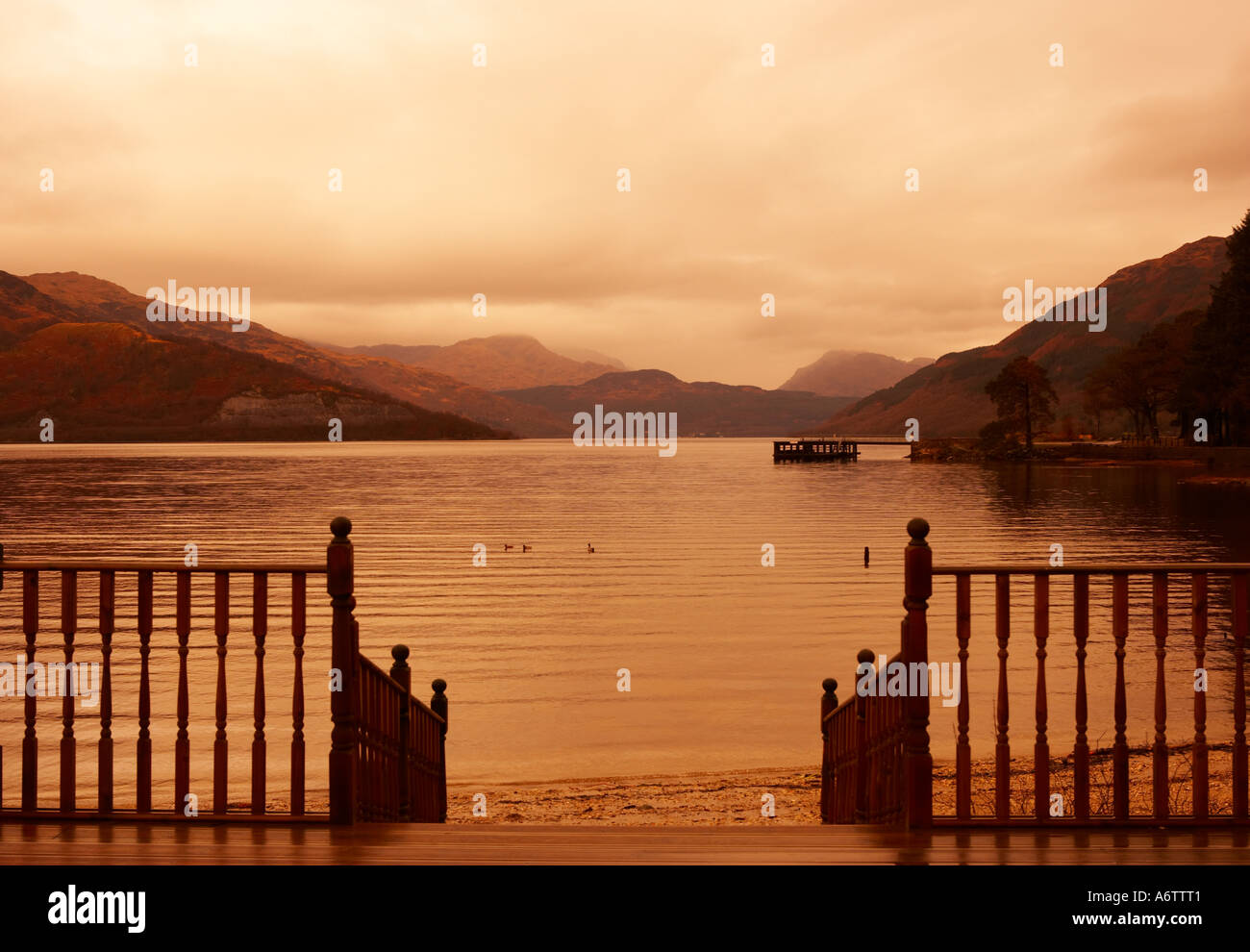 VIEW OF LOCH LOMOND AT TWILIGHT WITH MIST ON DISTANT HILLS FROM ROWARDENNAN LODGE STIRLING SCOTLAND - Stock Image