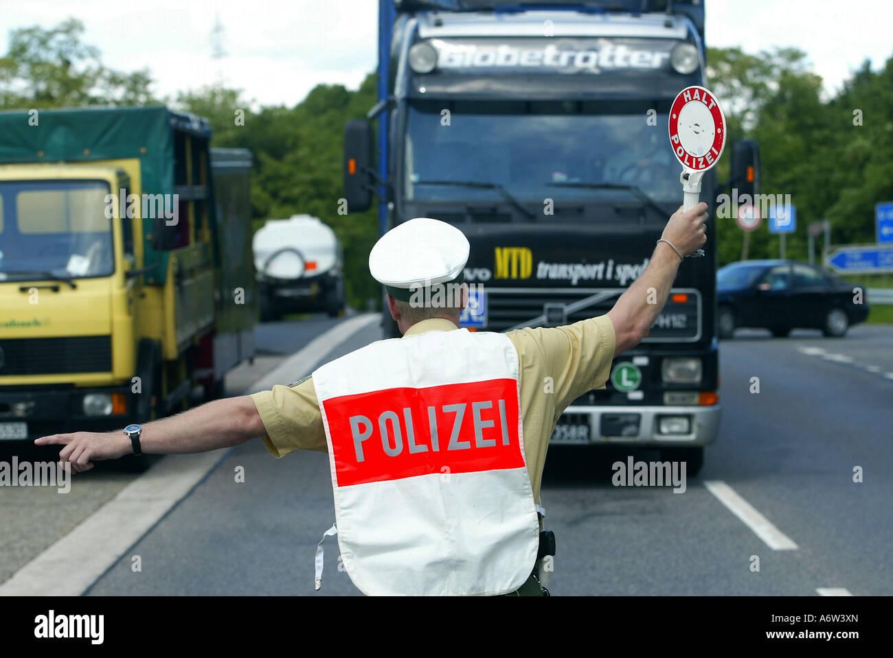 Policeman checks trucks Stock Photo
