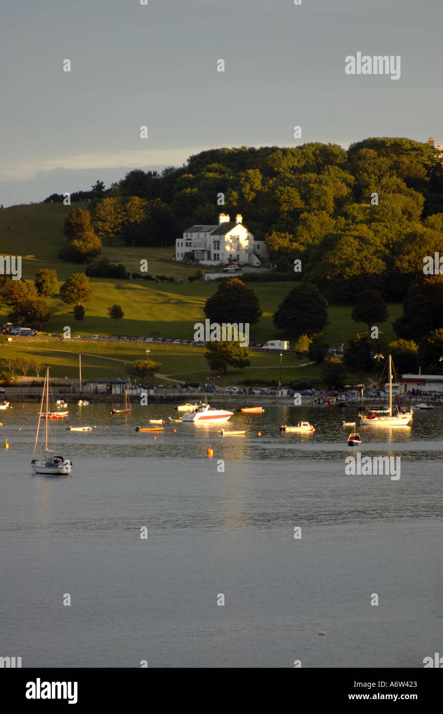 Peveril Point and harbour at Swanage at dusk White buildings picked out by evening sun dark sky and sea bobbing yachts - Stock Image