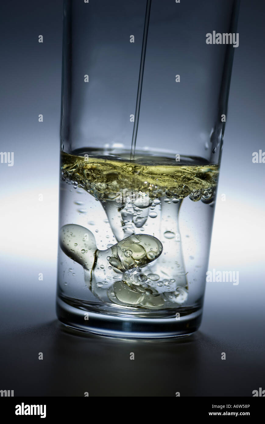 Oil poured in glass of water Stock Photo