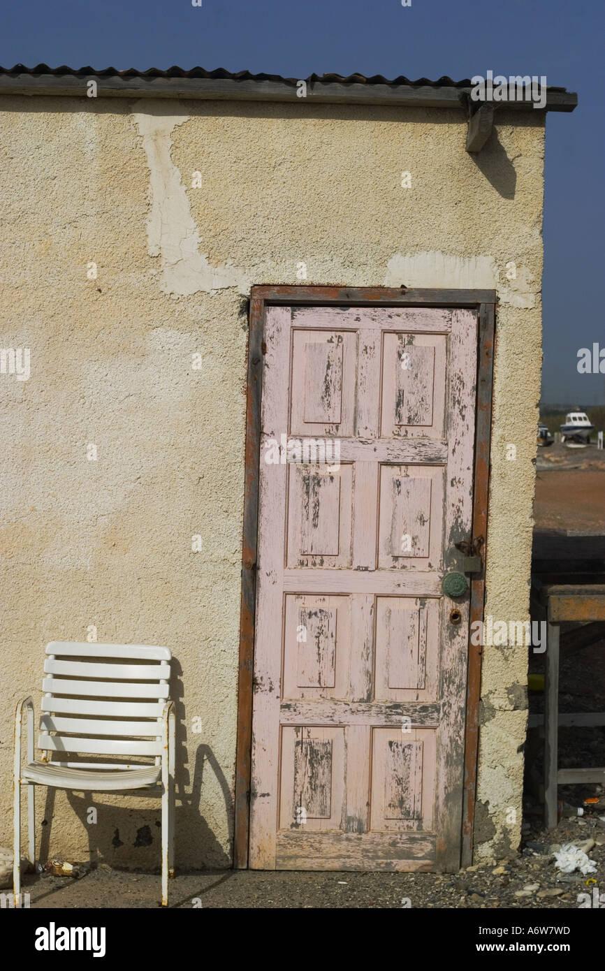A Delapidated Wooden Door In Cyprus With An Old Plastic Garden Chair