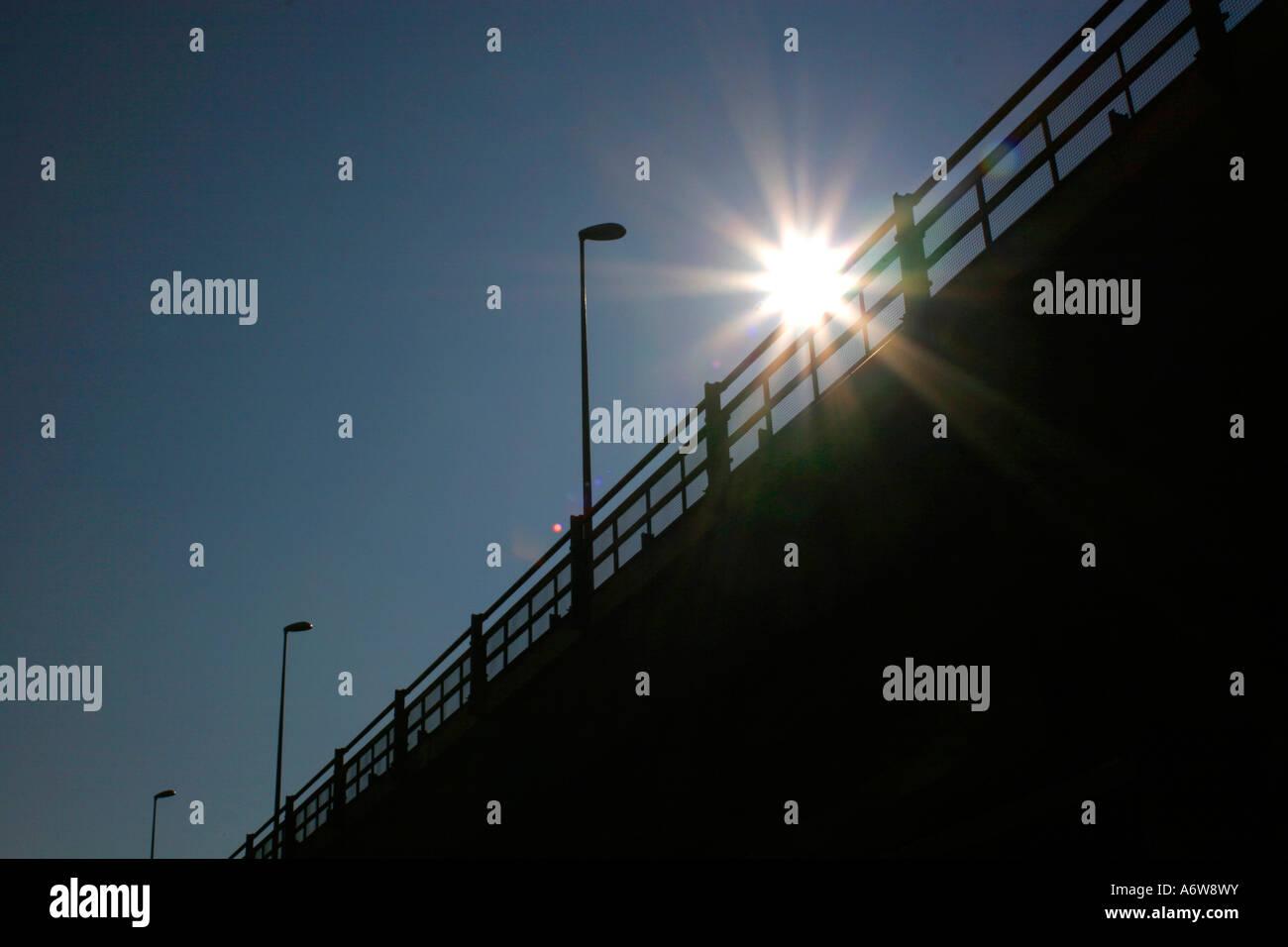 Silhouette of a bridge with a stellar sun - Stock Image