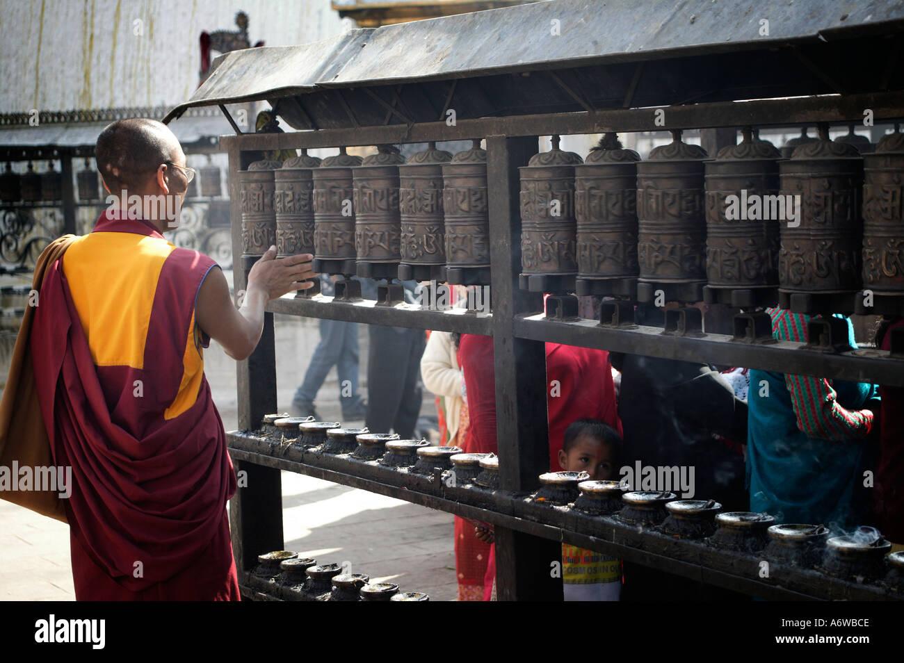 A Buddhist monk spinning prayer wheels at Kathmandu's monkey temple Nepal - Stock Image