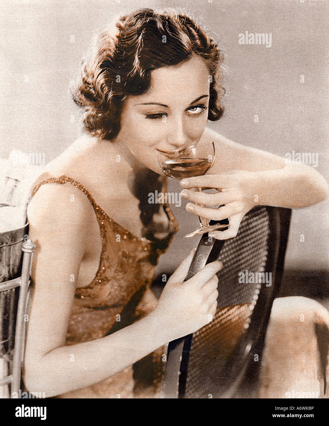 Champagne Wink 1932 photo from the English magazine London Life of a lady winking invitingly while sipping champagne - Stock Image