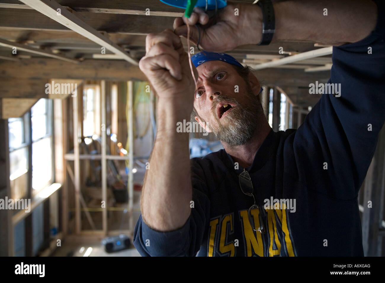 Volunteer Repairs Wiring in House Damaged by Hurricane Katrina - Stock Image