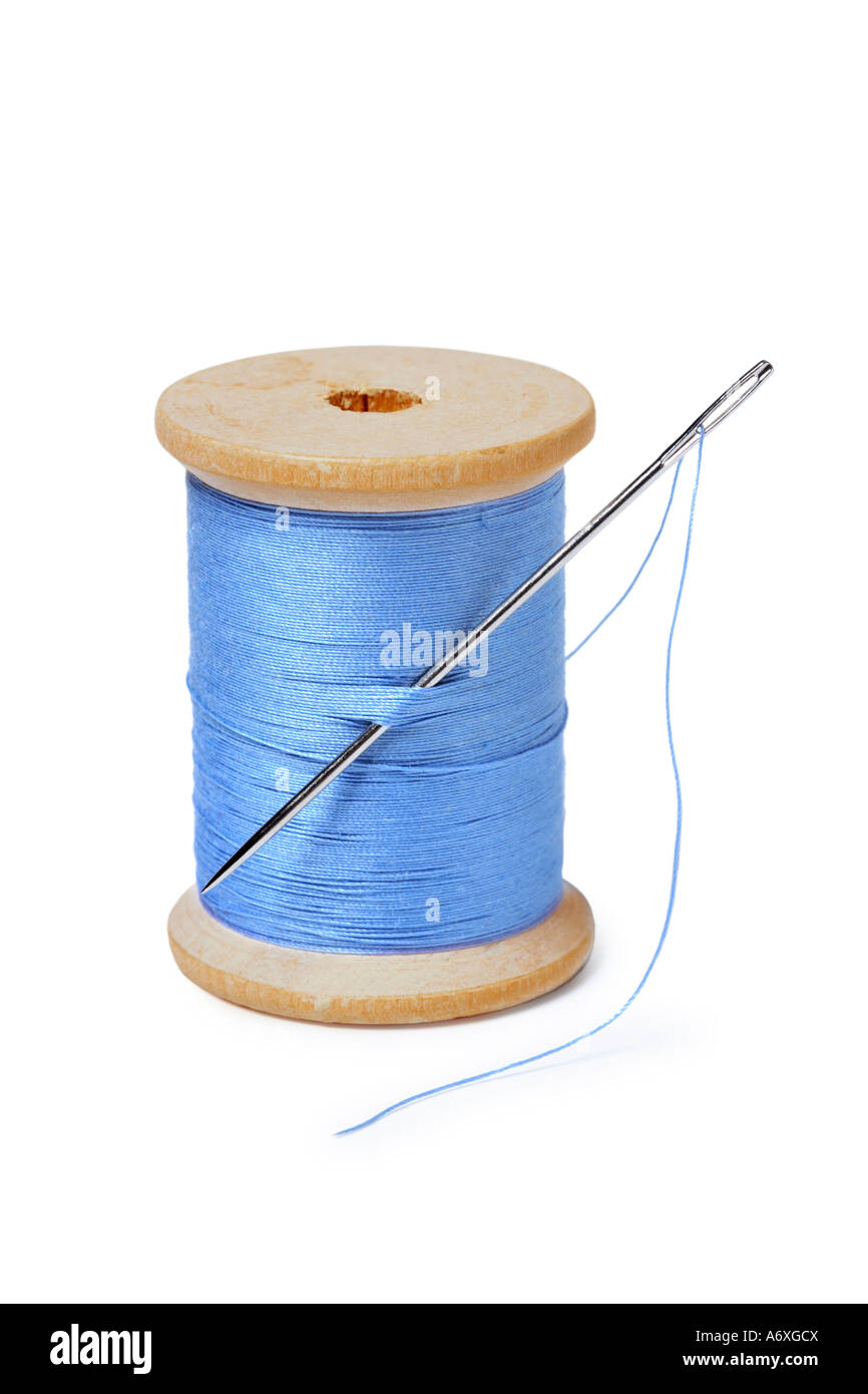 Spool of thread and needle cut out on white background - Stock Image