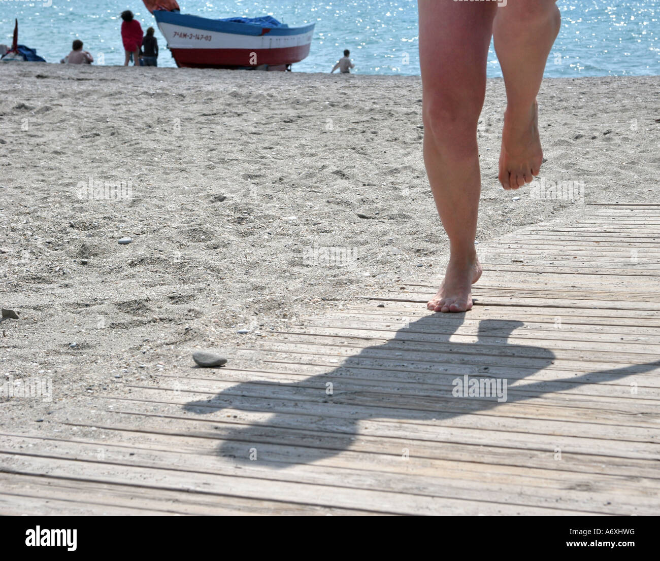 woman tip-toeing on hot boardwalk - Stock Image