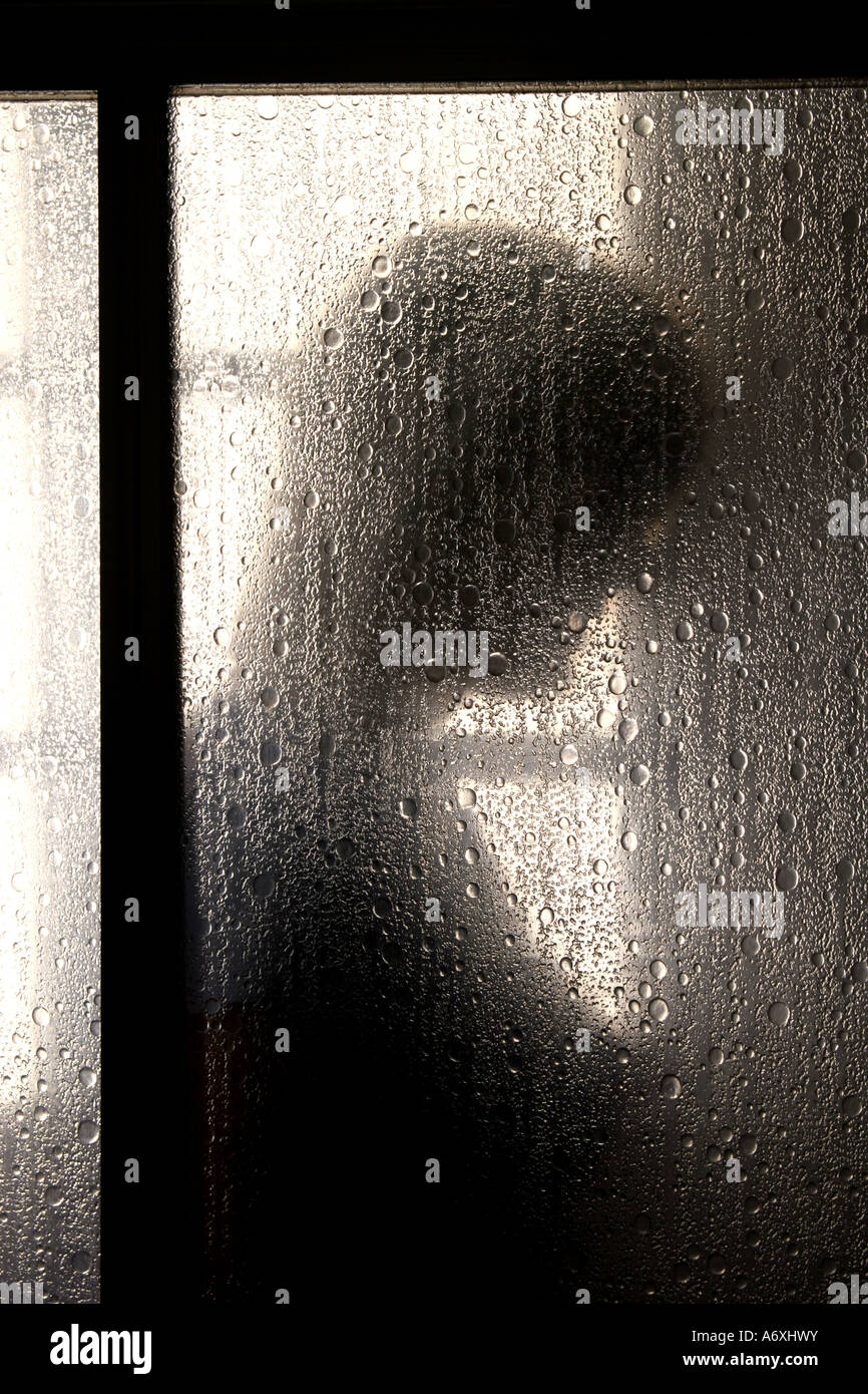 silhouette of a woman in shower cubicle - Stock Image