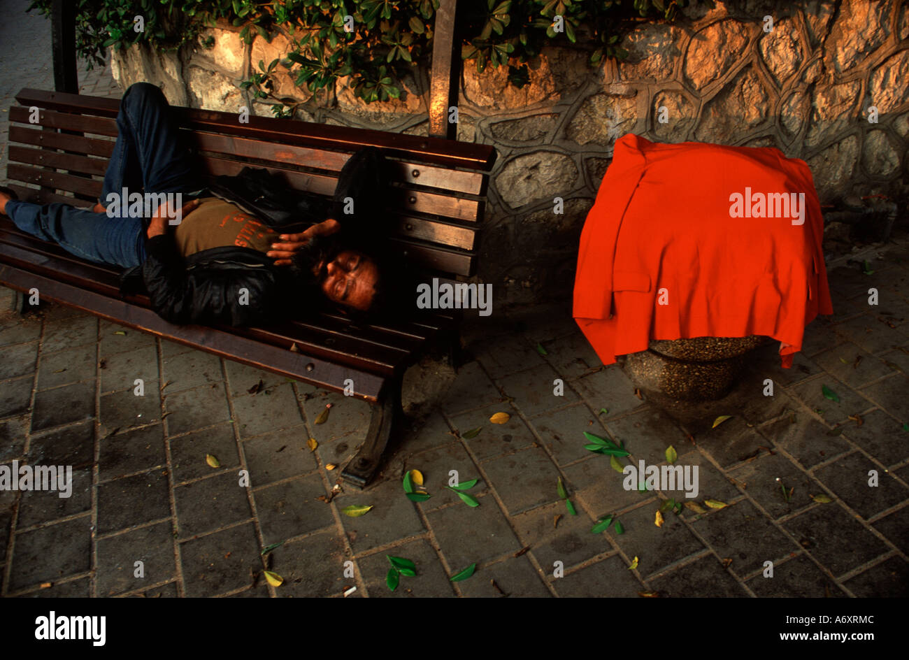 A homeless person sleeping on a bench downtown Tel Aviv Israel - Stock Image