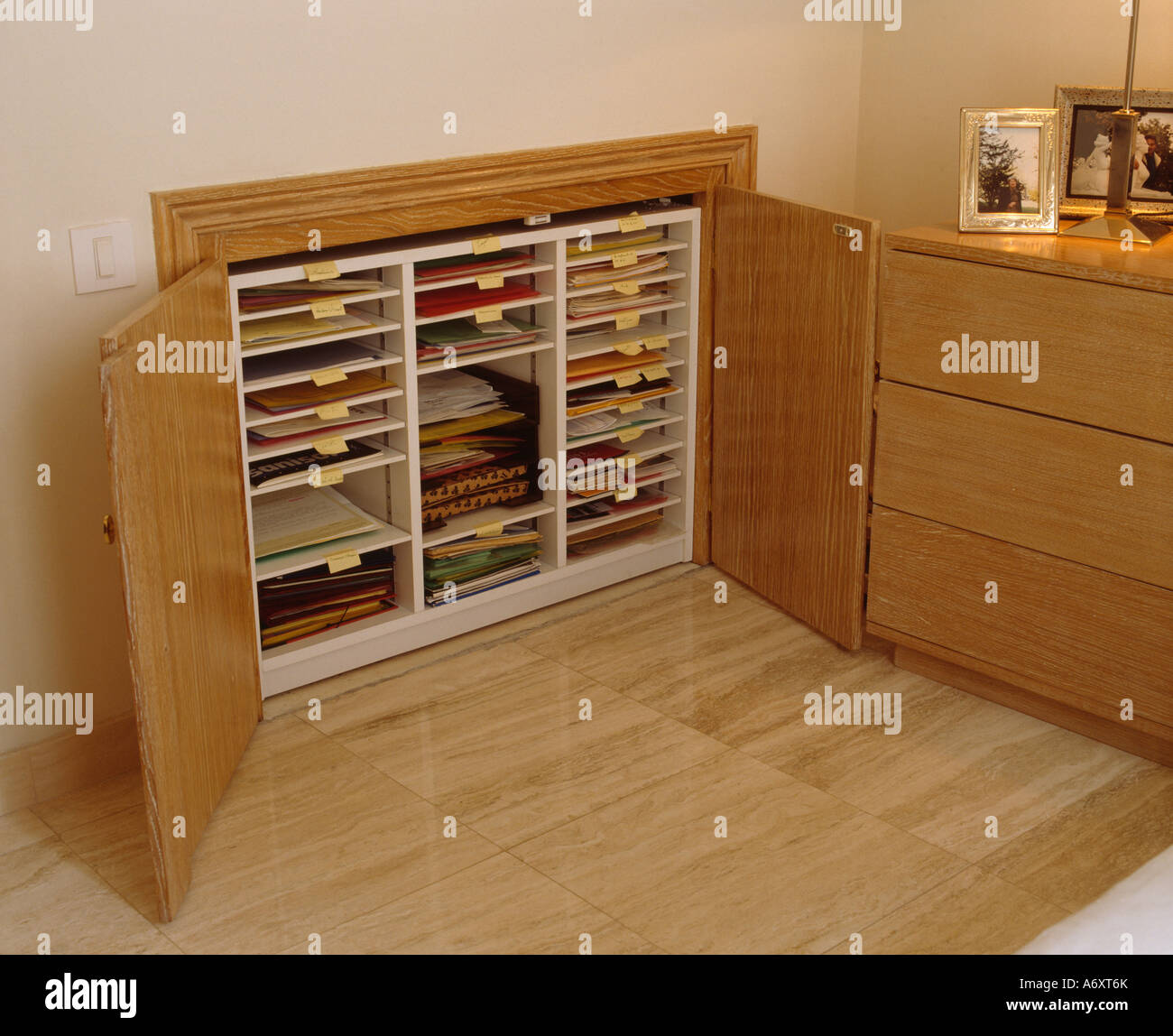 Close-up of plans shelves in recessed cupboard with wooden doors in wall of modern studio with wooden flooring - Stock Image
