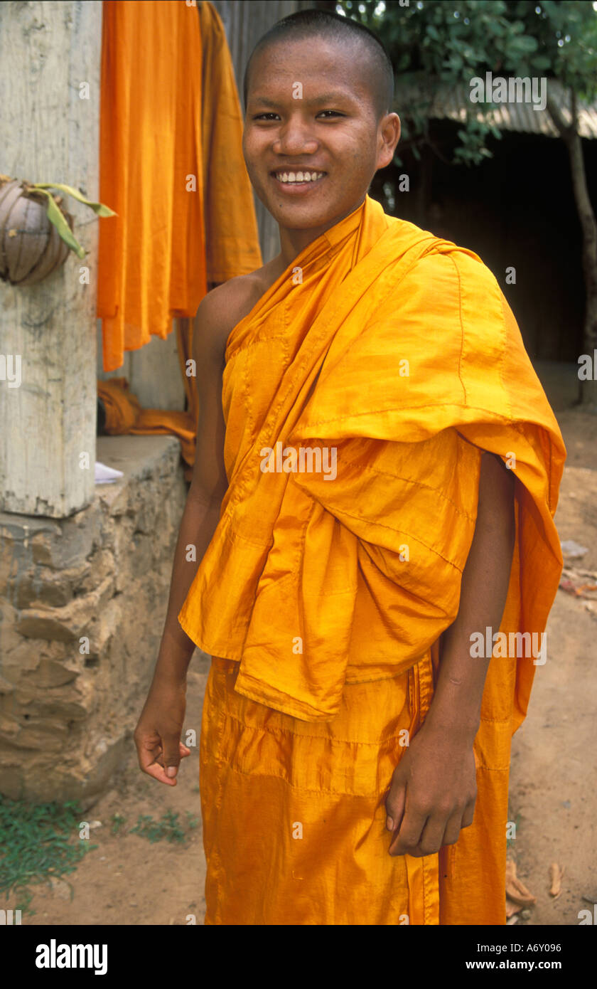 young trainee Buddhist monk in yellow robes smiling in peace at a pagoda in  Cambodia