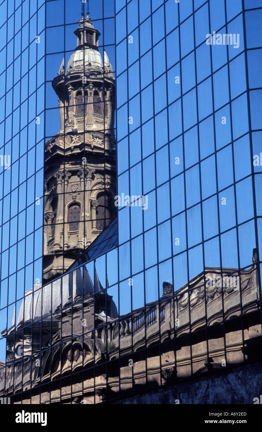 Tower of the Cathedral Plaza de Armas reflected in the modern mirrored facade of an adjacent building Santiago Chile - Stock Image