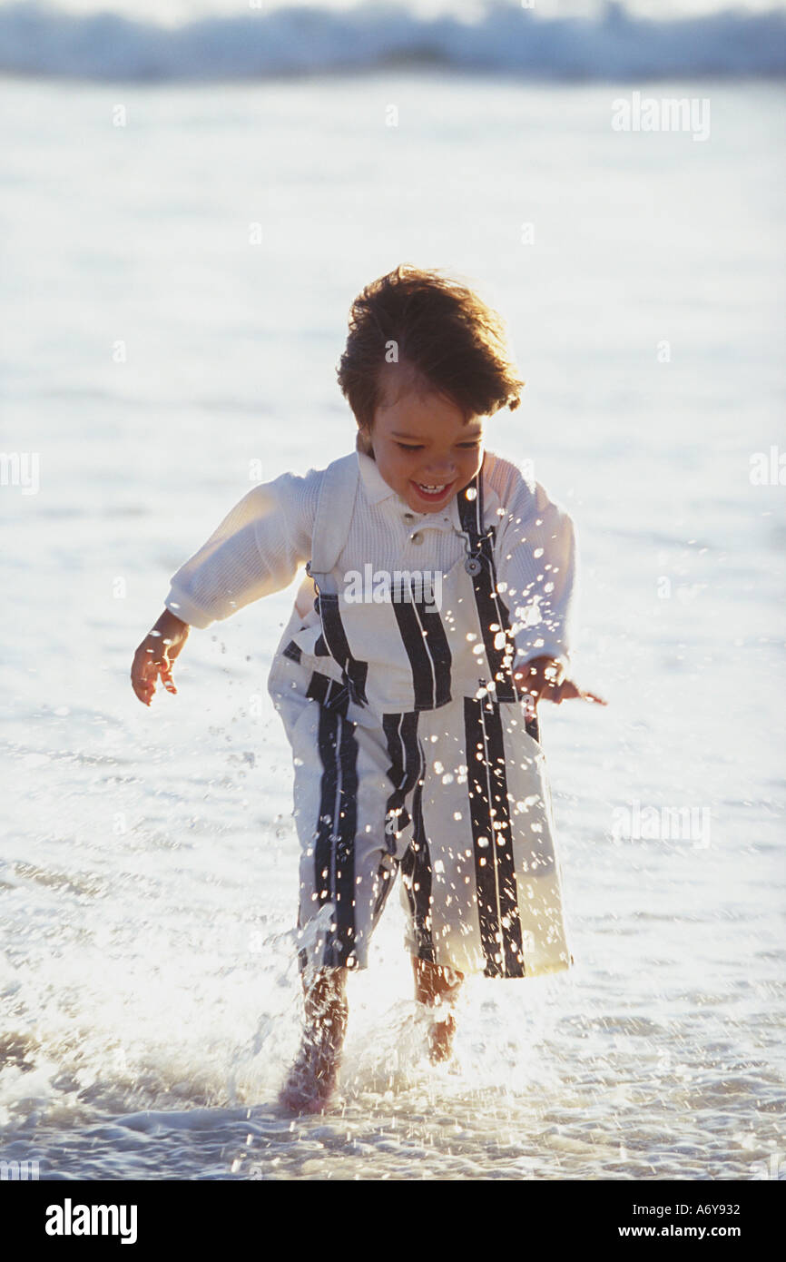 portrait of a boy running at the beach through the water Stock Photo