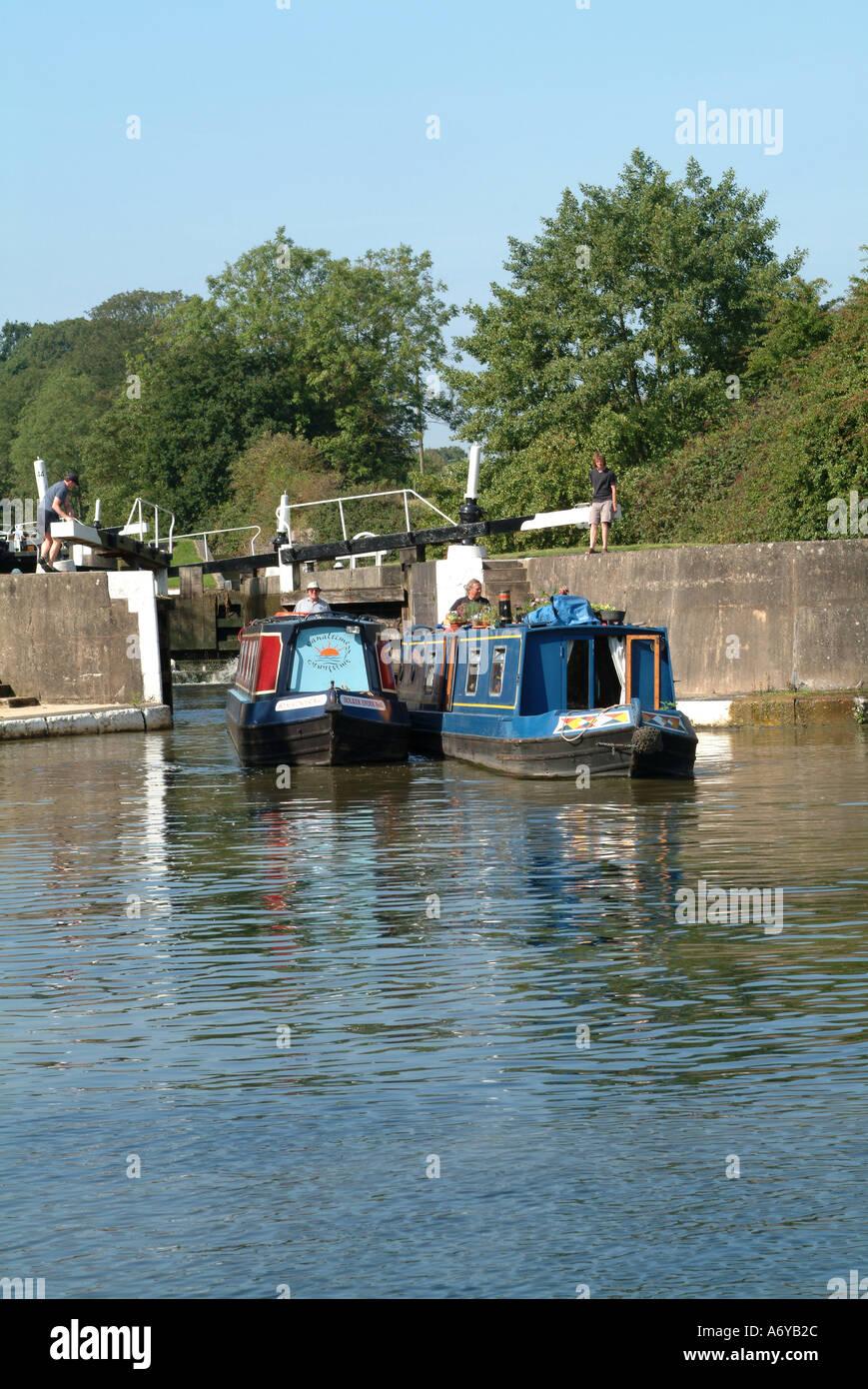 Narrow Boats Leaving Lock at Hatton Grand Union Canal Warwickshire England United Kingdom UK - Stock Image