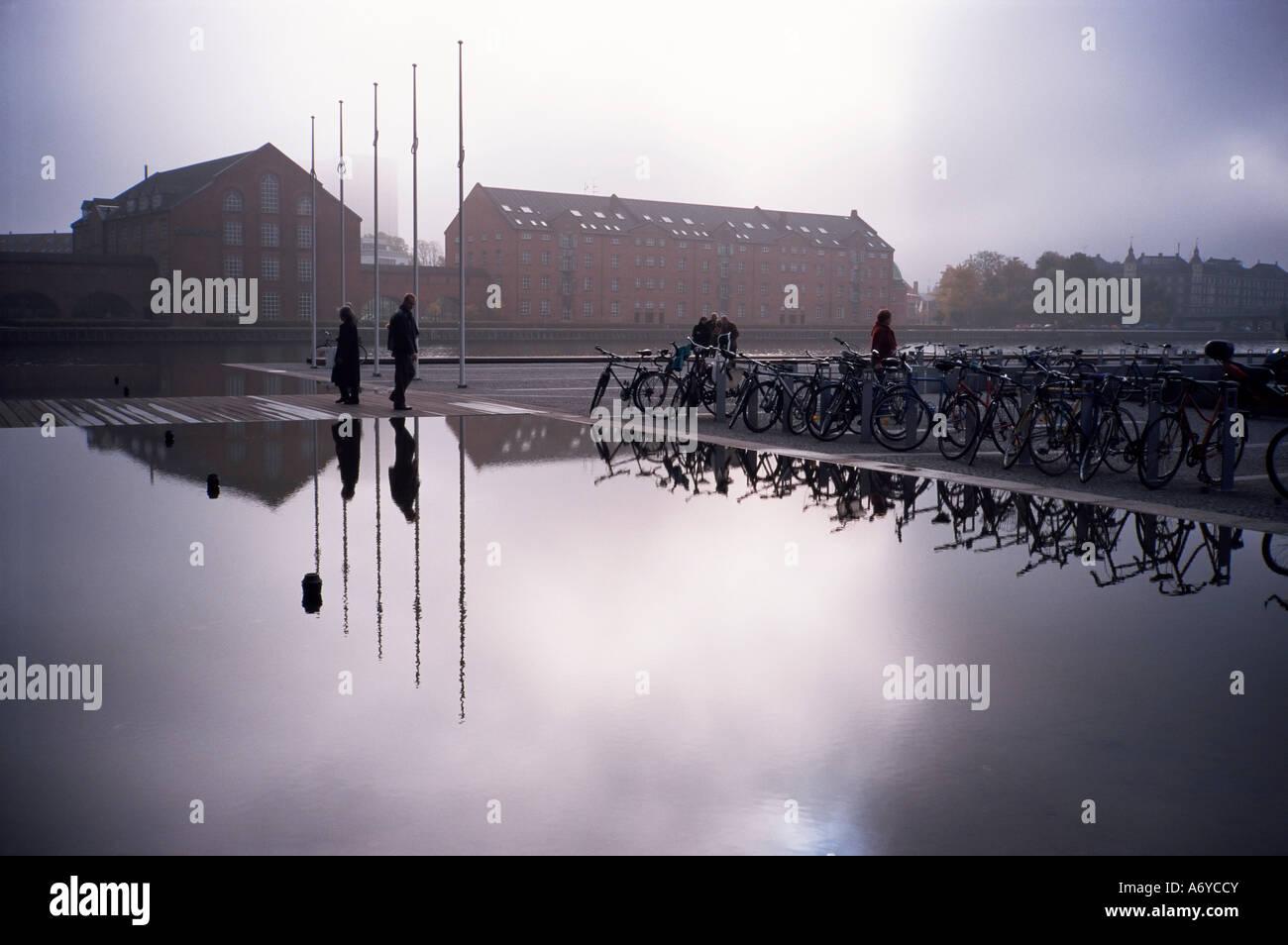 Bicycles reflected in still water Christians Brygge Copenhagen Denmark Scandinavia Europe - Stock Image