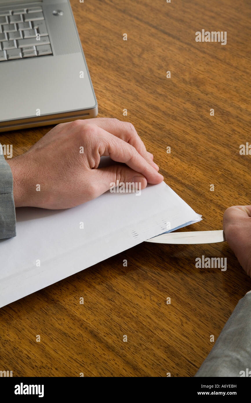 Businessman opening an envelope with a letter opener - Stock Image