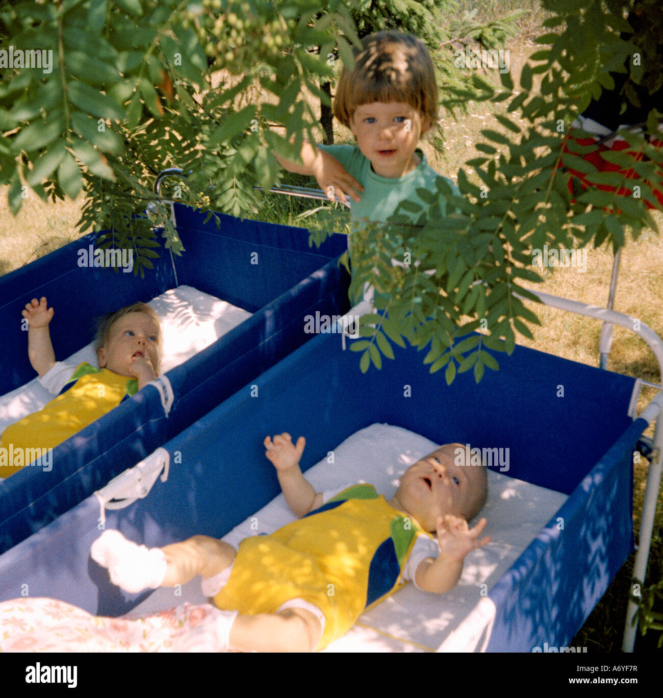 Child standing next to two baby cribs Stock Photo