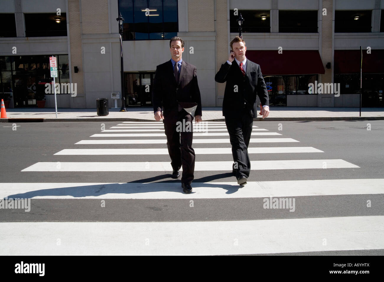 Two businessmen walking over a pedestrian crossing Stock Photo
