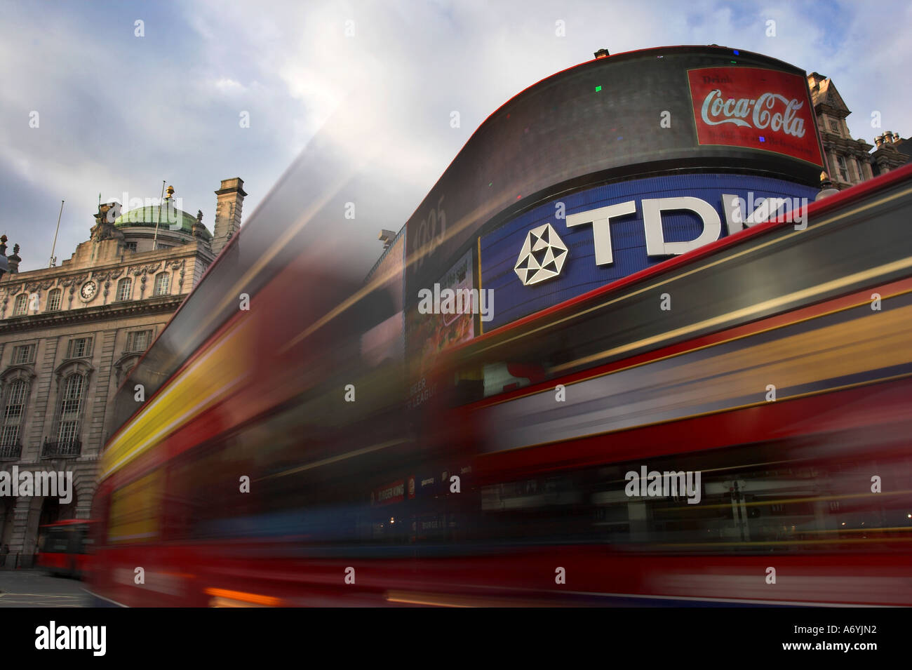 Picadilly Circus, London with bright billboards and two red double decker bus's blurred in foreground. - Stock Image