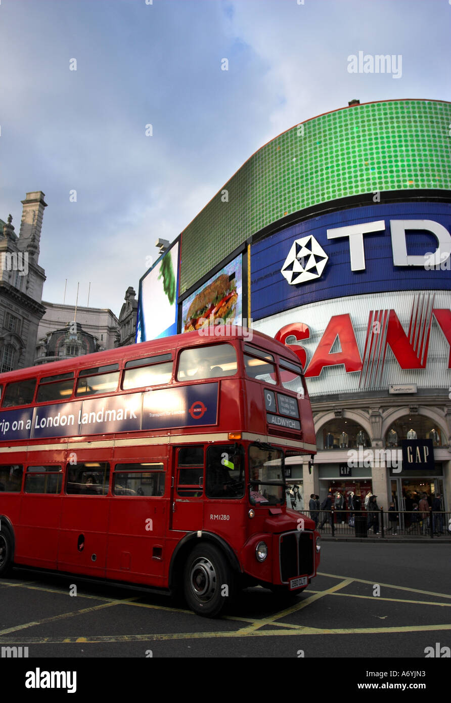 Picadilly Circus, London with bright billboards and old red double decker bus in foreground. - Stock Image