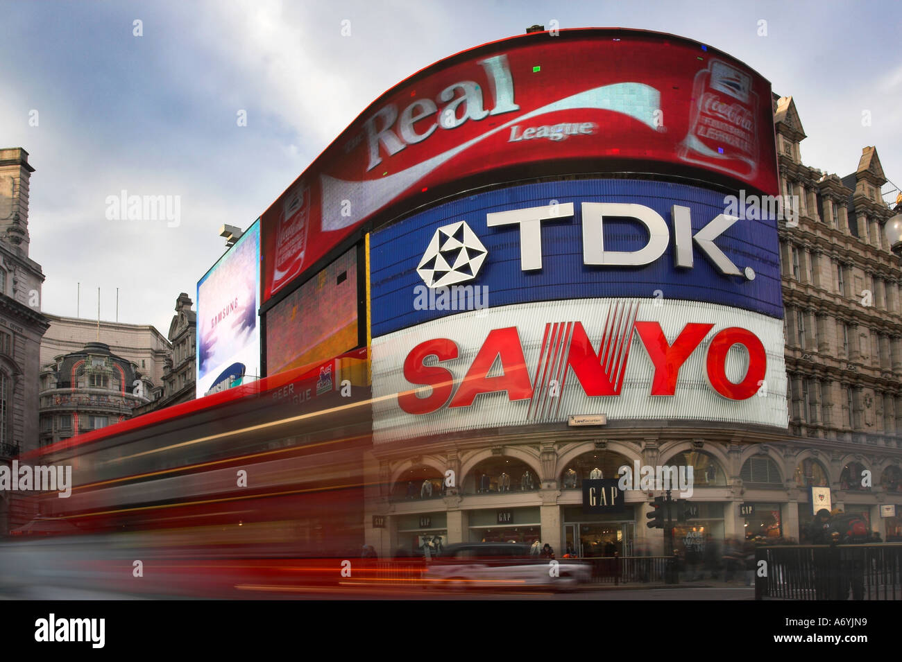 Picadilly Circus, London with bright billboards and red double decker bus blurred in foreground. - Stock Image