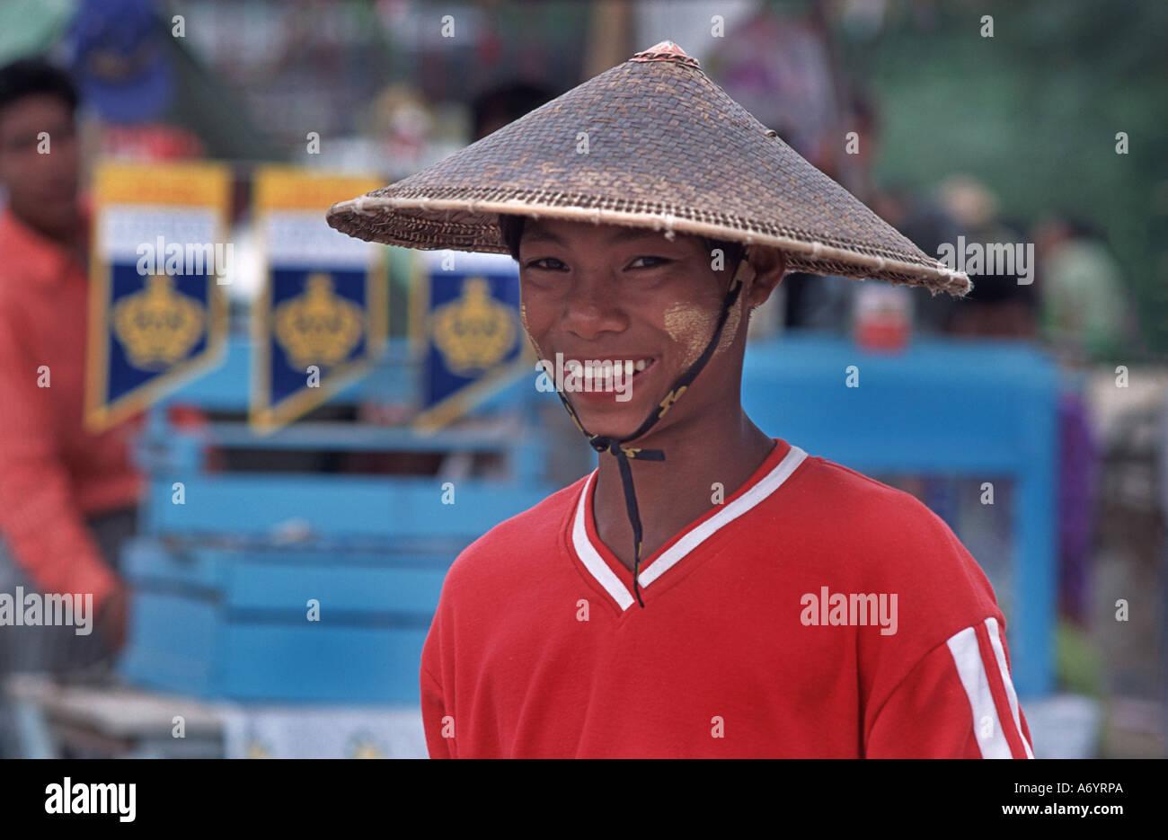 Friendly Burmese trader wearing a distinctive pointed hat Taungboyone August Nat Festival nr Mandalay Burma - Stock Image