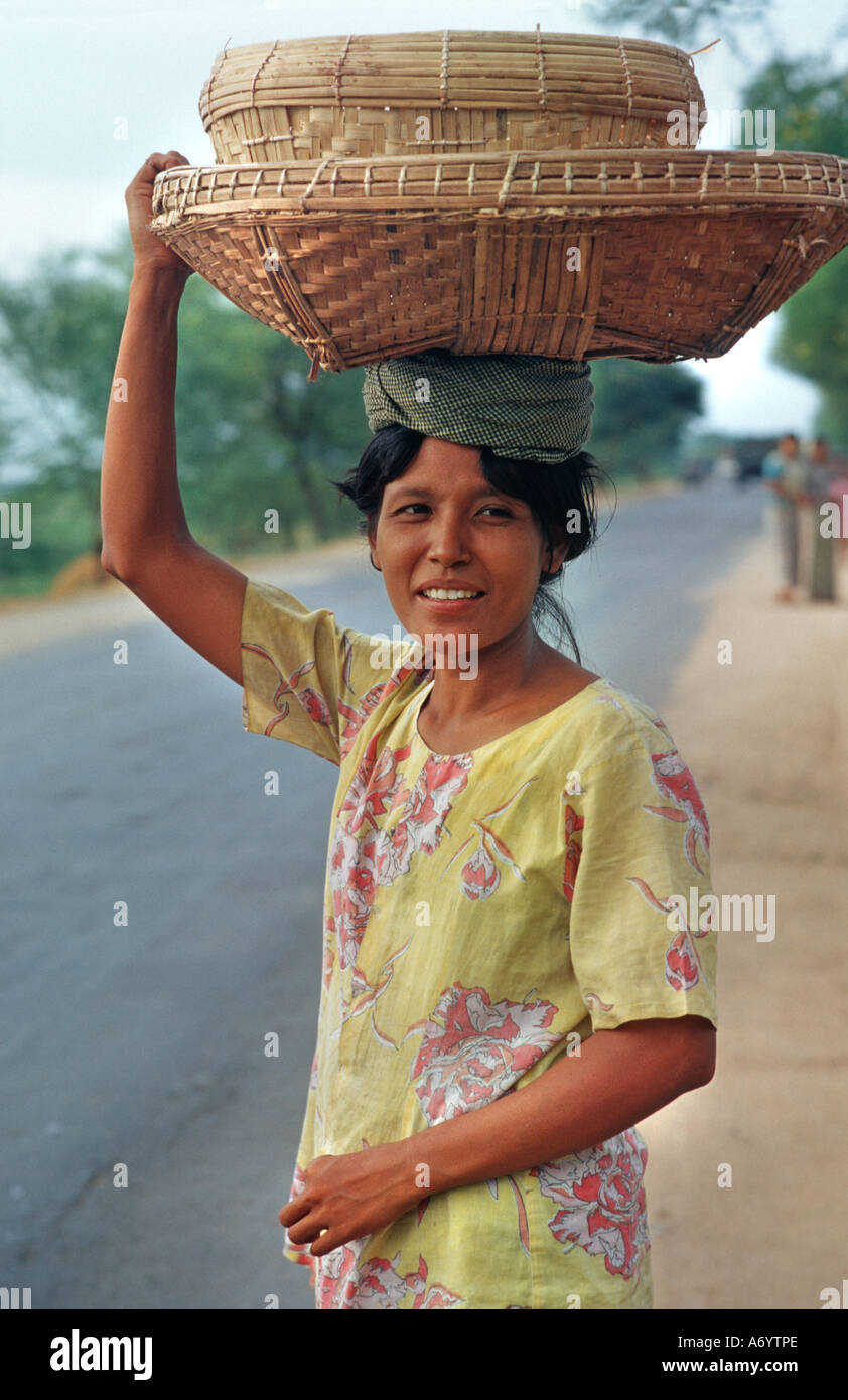 Friendly local woman carrying baskets on her head Nr Mandalay Burma Taungboyone Nat Festival August - Stock Image
